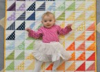 baby and rainbow quilt
